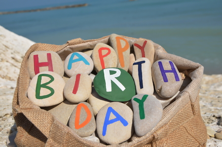Happy Birthday composition of stone letters in a bag Stock Photo