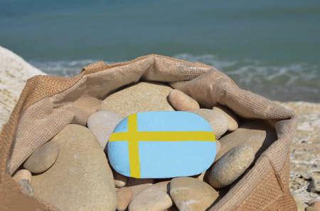 Çakıl taşları ile bir çanta içinde bir taş üzerinde İsveçli bayrağı Stock Photo