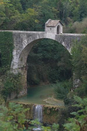 Cecco Bridge, a two-arched Roman bridge duty with little house Stock Photo