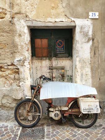Abandoned old rusty motorbike in front of door