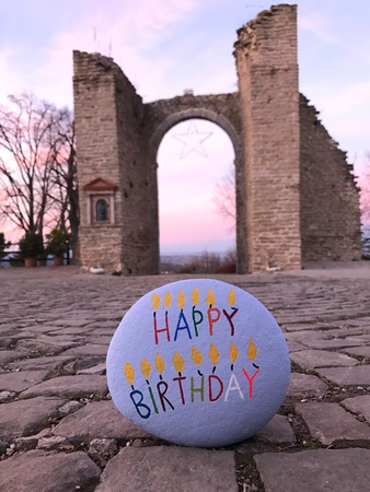 Happy Birthday message on a stone on a ground