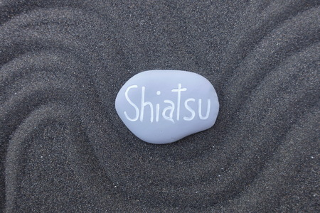Shiatsu word carved on a gray painted stone over black Stock Photo