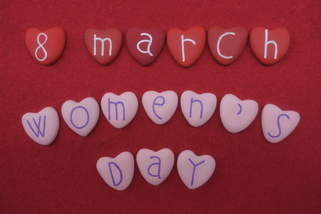 8 March, Womens Day with red and pink colored heart stones over red sand