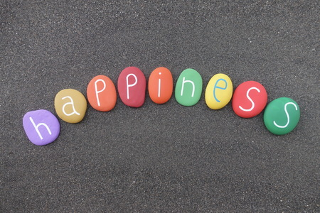 Happiness word with multicolored stones over black Stock Photo