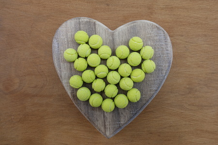 Yellow tennis ball sweets on a wooden heart