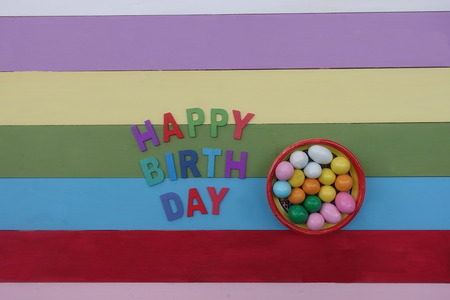 Happy Birthday with multi colored wooden letters and chocolates Banque d'images - 122833005