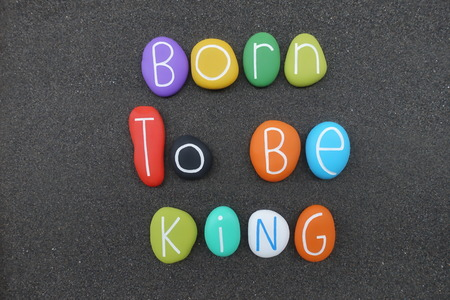 Born to Be King, composed birthday phrase with multi colored sea stones over natural black volcanic sand