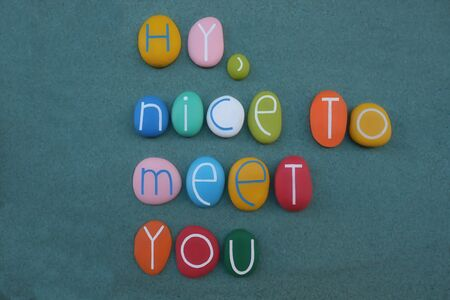 Hy, nice to meet you, creative text composed with multi colored stone letters over green sand