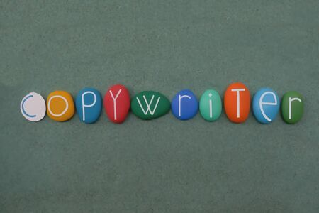 Copywriter, act or occupation of writing text for the purpose of advertising or other forms of marketing composed with multi colored stone letters over green sand 스톡 콘텐츠