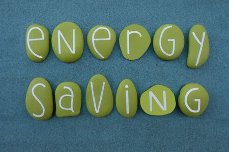 Energy Saving text composed with green colored stone letters over green sand