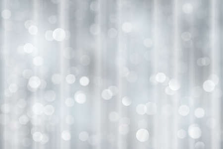 festive occasions: Light effects and sparkling out of focus lights for a magical abstract silver backdrop for the festive Christmas, holiday season to come.