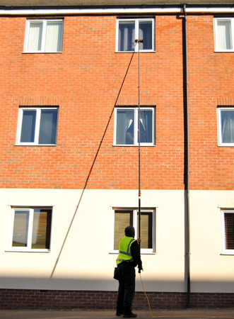 Man washing apartment windows with a very long pole 写真素材 - 117502173