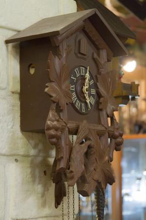 reloj cucu: Un reloj de cuco vieja hecha de madera colgado en la pared. De cerca.
