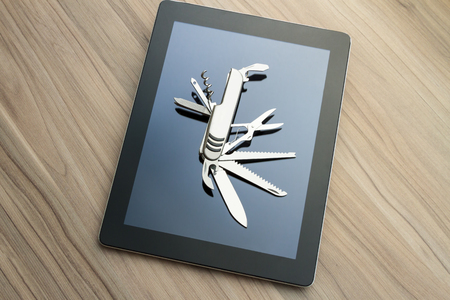multitask: Silver penknife on a tablet screen. Conceptual image for digital tools, multi-task devices, software utilities, innovation and versatility. High angle view. Copy space. Stock Photo