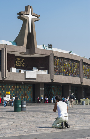 believing: Mexico City, Mexico - May 25, 2011: A pilgrim prays on his knees before the Basilica of Our Lady Guadalupe. This church is one of the most popular pilgrimage sites of Catholicism around the world. The new Basilica was built in 1976, next to the old one. Editorial