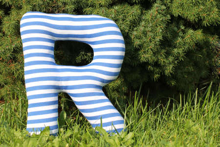 sward: Striped textile letter on sward in the garden Stock Photo