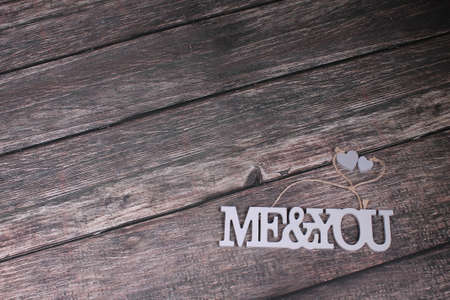 Grey letters me and you with little hearts on wooden background