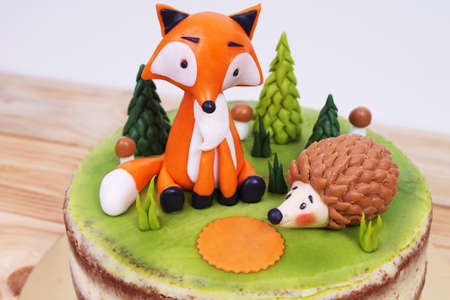 Birthday naked cake with fox and hedgehog from almond paste in detail on wooden background Banque d'images