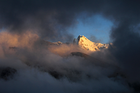 snowcovered: Huantsan mountain peak with clouds and late sun in the peruvian Cordillera Blanca Stock Photo