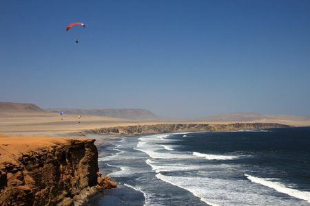 oceanfront: Paraglider soaring over the cliffs at oceanfront of Paracas Peru