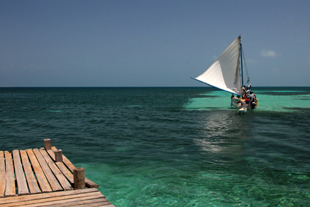 Wooden pier and sailing ship, Tobacco Caye, Belize, Central America