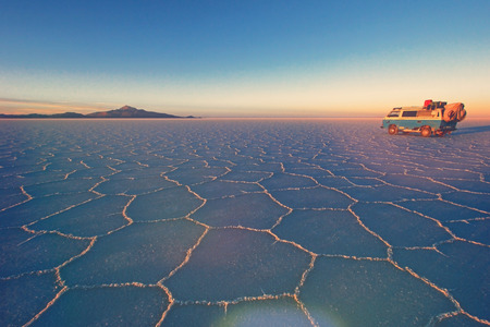 Old german vintage campervan on Salar de Uyuni, salt lake, is largest salt flat in the world, altiplano, retro vintage photo filter effect in pastell colers with light leaks and increased exposure, Bolivia, South America