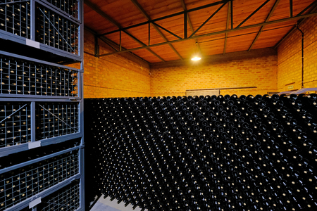 Resting wine bottles stacked in the cellar of a Malbec winery factory, San Juan, Argentina, South America, also seen in Mendoza
