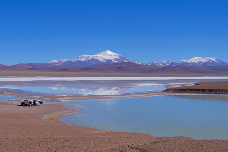 Camping vehicles standing by the Lagoon Laguna Brava, near Paso Pircas Negras mountain pass, snow covered mountains in the background, Argentina, La Rioja, South America Stock Photo