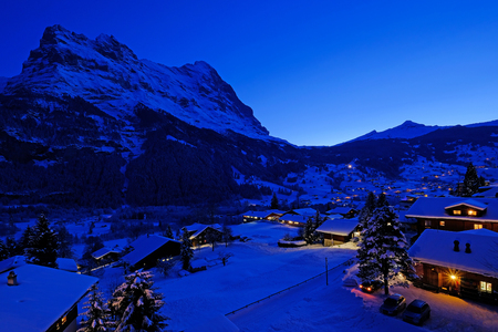 Grindelwald village at dusk with Mt. Eiger peak in the background, snow covered landscape in winter, Grindelwald, Bern, Switzerland, Europe Zdjęcie Seryjne