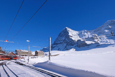 The Jungfrau railway train station at Kleine Scheidegg leading to Jungfraujoch, peak and the famous north face of mount Eiger and Monch in the background, Bern, Switzerland, Europe