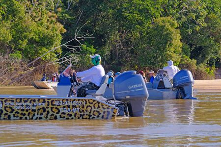PORTO JOFRE, MATO GROSSO, BRAZIL, JULY 27, 2018: Tourists, pilot and guide on a boat excursion for Jaguar and wildlife watching, Pantanal, Brazil on July 27, 2018