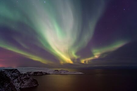 Intensa aurora boreal, Aurora Boreal sobre la isla Knivskjelloden, vista desde Nordkapp, Cabo Norte, el punto más septentrional de Europa, Finnmark, Noruega