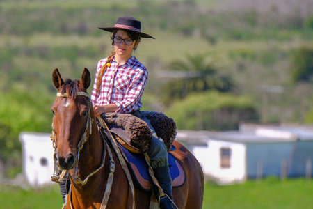 CAMINOS, CANELONES, URUGUAY, OCT 7, 2018: Female gaucho riding on a horse at a Criolla Festival in Uruguay, South America, also been seen in Argentina, Brazil and Chile Editorial