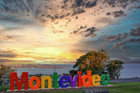 Montevideo symbolic sign and panoramic view of west coast of Montevideo from Fortaleza General Artigas fortress with a beautiful cloudy sky at sunset, Montevideo, Uruguay, South America