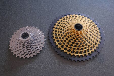 Rear mountain bike cassette, size comparison 12-speed vs 8-speed, big and small, in silver and golden color, the big 12-speed one is a 10-50 teeth