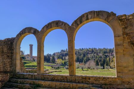 Close up of the preserved roman arches, the theatre amphitheater and the tower of the San Romolo Cathedral in the background, I century BC, Fiesole, Florence, Tuscany, Italy, Europe