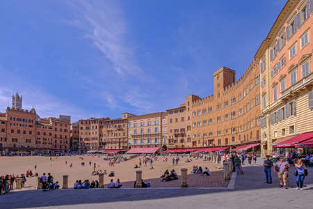 Siena, Tuscany, Italy, April 01, 2019: Tourists at the Piazza Del Campo Square, the historic centre of Siena, Tuscany, Italy, Europe. Declared by UNESCO as a World Heritage Site