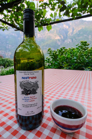 Ludiano, Ticino, Switzerland, June 04, 2019: Nostrano Red wine bottle and famous ceramic boccalino mug on table under the pergola in the traditional rock grotto restaurant Spruch, Ludiano, Switzerland Editöryel