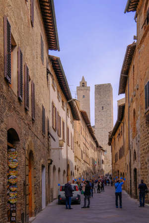 San Gimignano, Tuscany, Italy, April 02, 2019: TTourists in the streets of San Gimignano, the towers in the background, Tuscany, Italy, Europe