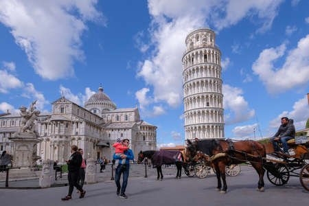 Pisa, Tuscany, Italy, April 05, 2019: Many tourists visit Piazza Dei Miracoli square with the famous Leaning Tower, babtistery and dome. Unesco World Heritage Site in Tuscany, Italy Editöryel
