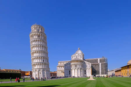 Pisa, Tuscany, Italy, April 05, 2019: Many tourists visit Piazza Dei Miracoli square with the famous Leaning Tower. Unesco World Heritage Site in Tuscany, Italy. Perfectly aligned tilt shift photo