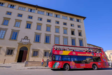 Fiesole, Tuscany, Italy, March 30, 2019: Red hop on hop off touristic city sightseeing bus in front of Seminario Vescovile, Fiesole, Florence, Tuscany, Italy, Europe