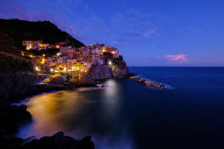 Colorful traditional houses on the rock over Mediterranean sea on dramatic sunset, Manarola, Cinque Terre, Italy, Europe
