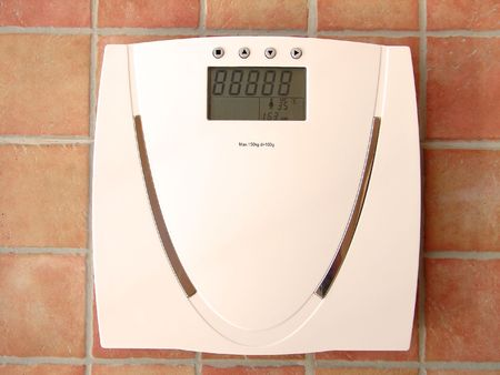 un healthy: Digital bathroom scale with tiles in background