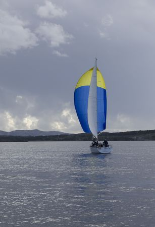 spinnaker: Yacht with blue and yellow spinnaker Stock Photo