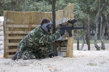 teambuilding: Paintball player in camouflage uniform and mask
