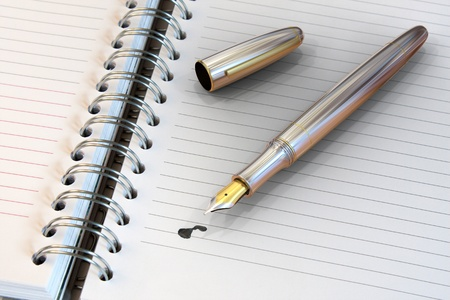 pad and pen: Metal fountain pen on notebook with ink drop Stock Photo