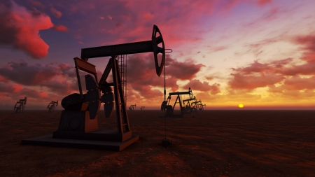 Oil field pump jacks at  sunset Stock Photo