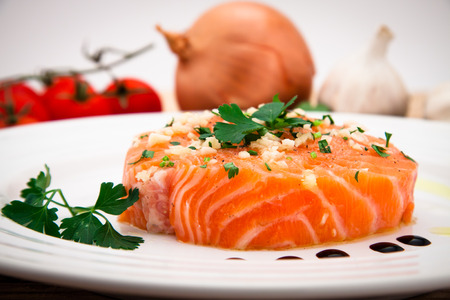 Marinated salmon filet with olive oil, parsley, garlic on plate photo