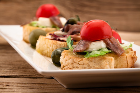 Crostini vith mozzarella cheese anchowy and tomato on wooden board photo